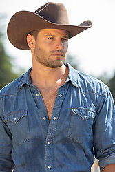 hot rugged cowboy on a ranch portrait of a hot All American cowboy