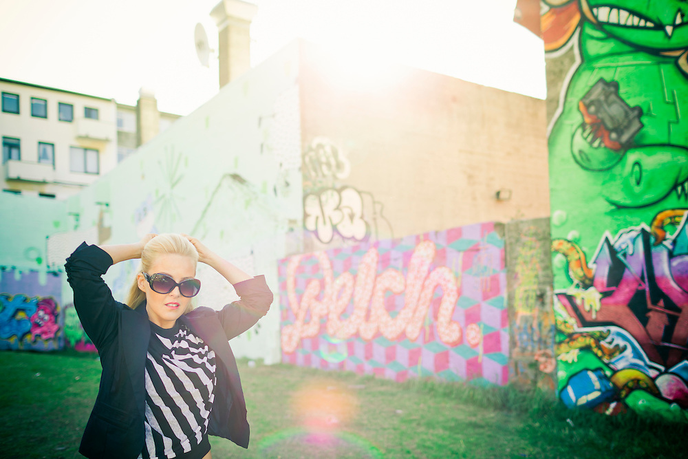 A young woman posing in the sun with graffiti walls behind her