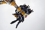 Nederland, Nijmegen, 3-10-2009Een bezoeker van de kermis hangt op zijn kop in een apparaat wat met grote snelheid ronddraait. Hij heeft zijn handen los in de lucht zodat hij alleen door de veiligheidsbeugel vastgehouden wordt.Foto: Flip Franssen/Hollandse Hoogte
