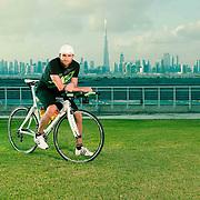 Triathlete portrait taken at Meydan Racecourse with the dramatic Dubai skyline behind.