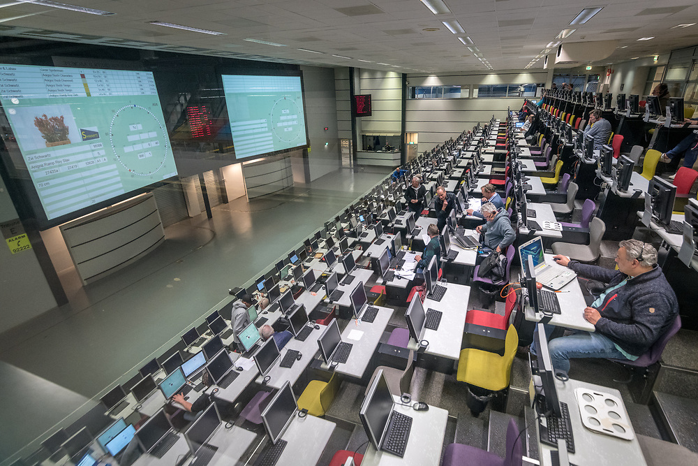 People sit at computers placing bids in the control center at the worlds largest flower auction, Royal Flora Holland and scan flower bids. Amsterdam, Netherlands