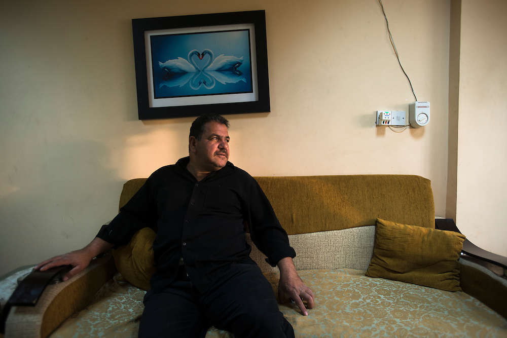 An Iraqi Christian from the town of Samarra in his living room. Following the 2003 Iraq war, he says foreign groups - Al-Qaeda, Salafists and other extremists - infiltrated the city. As Christians, he and his family began receiving threats and his brother's car was blown up. The entire family decided to move to Ainkawa, a largely Christian town in Iraqi Kurdistan. Relative security and the large influx of displaced people and refugees has caused prices to increase dramatically in the region. He must work three jobs just to pay rent on a small apartment for himself, his wife and their two sons. Iraq's Christian community is considered one of the longest continues Christian communities in the world. Violence, persecution and sectarian strife have forced more than two thirds of the Christian population to flee the country.  Ainkawa, Iraq. 17/04/2014.