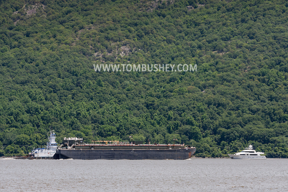 Cornwall-on-Hudson, New York - A tugboat pushes a barge south on the Hudson River as a smaller ship heads north in a view from Cornwall Landing on June 20, 2014. ©Tom Bushey / The Image Works