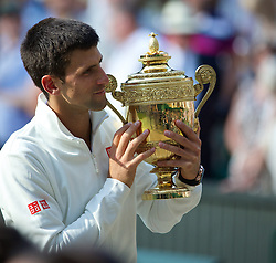 LONDON, ENGLAND - Sunday, July 6, 2014: Novak Djokovic (SRB) celebrates by kissing the trophy after winning the Gentlemen's Singles Final match 6-7 (7), 6-4, 7-6 (4), 5-7 (4), 6-4 on day thirteen of the Wimbledon Lawn Tennis Championships at the All England Lawn Tennis and Croquet Club. (Pic by David Rawcliffe/Propaganda)