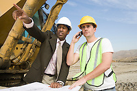 Surveyor and construction worker with blueprints