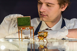 "© Licensed to London News Pictures. 31/05/2019. LONDON, UK. A technician presents ""A fine and rare Fabergé gold and enamel miniature bonbonnière chair"" by workmaster Michael Perchin, circa 1900, and ""A fine and rare Fabergé vari-colored gold, guilloché enamel and nephrite miniature table bonbonnière"" by workmaster Michael Perchin, 1899-1908, (Est: £800,000 – 1.2 million) at a preview of works from the upcoming sale of Russian Pictures, Works of Art, Fabergé & Icons Sales at Sotheby's, New Bond Street, on 4 June 2019.  Photo credit: Stephen Chung/LNP"