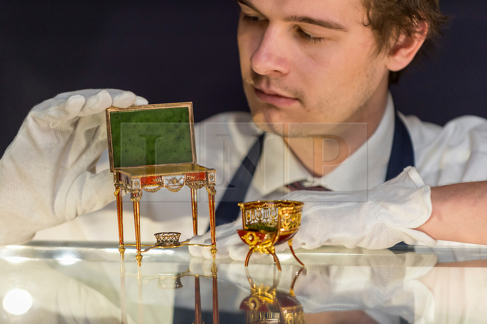 """© Licensed to London News Pictures. 31/05/2019. LONDON, UK. A technician presents """"A fine and rare Fabergé gold and enamel miniature bonbonnière chair"""" by workmaster Michael Perchin, circa 1900, and """"A fine and rare Fabergé vari-colored gold, guilloché enamel and nephrite miniature table bonbonnière"""" by workmaster Michael Perchin, 1899-1908, (Est: £800,000 – 1.2 million) at a preview of works from the upcoming sale of Russian Pictures, Works of Art, Fabergé & Icons Sales at Sotheby's, New Bond Street, on 4 June 2019.  Photo credit: Stephen Chung/LNP"""