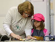 Linda Langenberg (from left), of Marion, gives some instructions to Naomi Box, 9, of Newhall during a meeting of the Cedar Valley Woodcarvers in Midway on Saturday, May 25, 2013.