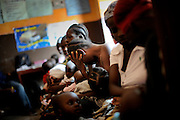 Women and their children waiting for help at the health care centre in Marbella slum, Freetown, Sierra Leone. Health care for pregnant women and young children is free since the beginning of 2010.