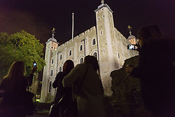 © Licensed to London News Pictures. 23/10/2013. London, UK. People take photographs as the Yeoman warder, Kevin Paul Kitcher, leads a twilight tour at the Tower of London which gives visitors a unique after hours view of the UK's most visited historic attraction. The first Twilight Tour at the Tower of London will take place on 3 November 2013 and they will then take place every Wednesday during November, then January, February and March in 2014.Photo credit : Vickie Flores/LNP