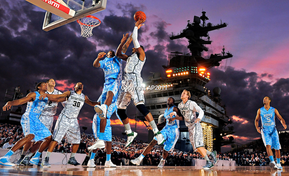 North Carolina forward John Henson (31) tries to block a shot by Michigan State center Adreian Payne (5) during the first half of the Carrier Classic NCAA college basketball game aboard the USS Carl Vinson, Friday, Nov. 11, 2011, in Coronado, Calif.  (AP Photo/Mark J. Terrill)