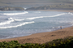 © Licensed to London News Pictures. 26/05/2020. Padstow, UK. A man stands in a wetsuit on Constantine Bay, Cornwall, after a man died after getting into difficulty in the sea between Constantine Bay and neighbouring Treyarnon Bay. A teenage girl also died after being trapped in a capsized rigid inflatable boat near Padstow. There were multiple other beach related incidents reported to emergency services over the bank holiday. Due to Coronavirus (COVID-19), the RNLI are currently not operating a Lifeguard service on the beaches in Cornwall, as there would be normally at this time of year. Photo credit : Tom Nicholson/LNP