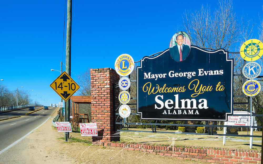 """A sign welcomes visitors to Selma, Alabama, Feb. 7, 2015. In the background is the Edmund Pettus Bridge, where civil rights activists were attacked by law enforcement during """"Bloody Sunday,"""" March 7, 1965. Mayor George Evans is only the second African-American in history to hold the mayoral position in the predominantly black city. (Photo by Carmen K. Sisson/Cloudybright)"""