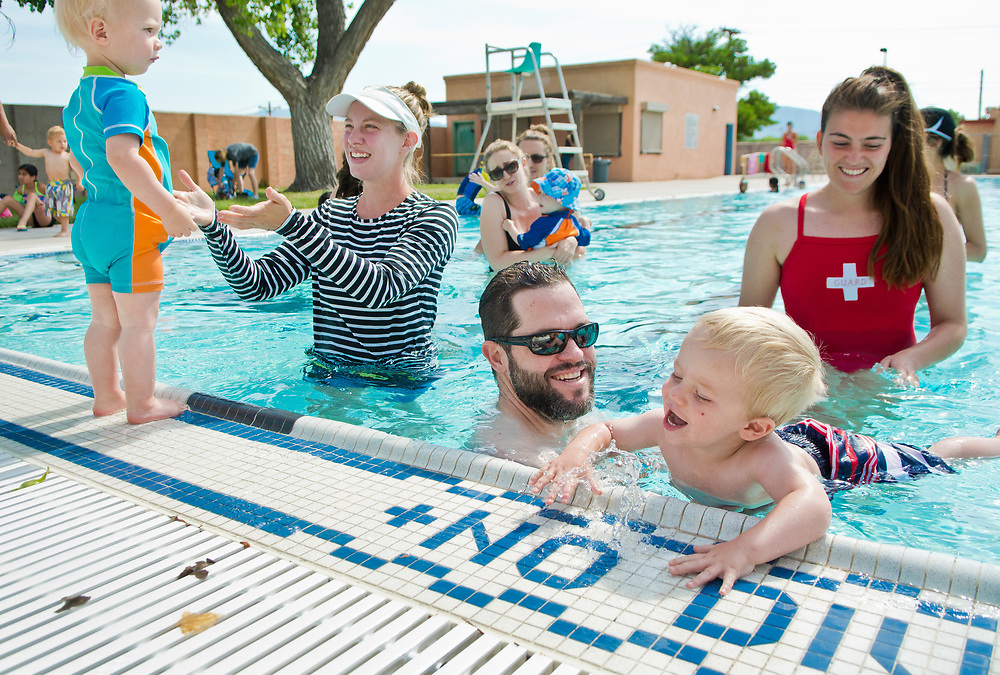"mkb060617h/metro/Marla Brose --  Kyle McMurray, second from right, holds his 21-month-old son Patrick, front right, as Rachel Versluis encourages her one-year-old son Emrys Detweiler to jump the Sunport Pool duirng a parent and tot swimming lesson at the city pool, Wednesday, June 7, 2017. Teaching the class is Olivia Gorham, back right. ""We get them to not be afraid of the water,"" said Gorham who has been teaching the class for the past four years. Swimming lessons are available at Sunport Pool and swimming pools throughout the city. Information about swimming lessons is available on the City of Albuquerque website. Registration and availabiltiy information for lessons can be found at each pool. (Marla Brose/Albuquerque Journal)"