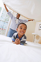 Father holding bed sheet over son (3-6)