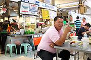 A man enjoys a seafood dinner inside the Or Tor Kor market in Bangkok Thailand.