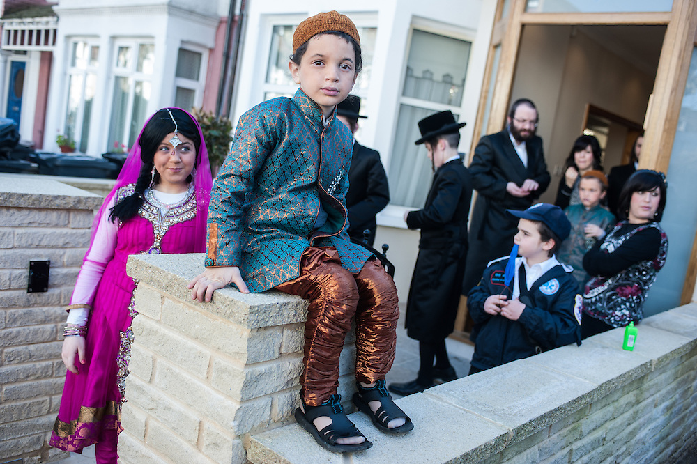 London, UK - 16 March 2014: Dressed in fancy clothes young men from the Orthodox Jewish community of Stamford Hill celebrate the festivity of Purim, dancing and singing in the streets at the sound of Yiddish music and visiting wealthy businessmen collecting for their charity