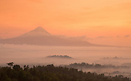 Mount Merapi volcano at sunrise with Borobudor Temple rising through the clouds in Central Java, Indonesia.