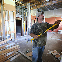 Ethan Page, a worker with Murphy and Son General Contractors out if Southaven, works on taking down old sheetrock and framing at the CVB office in Tupelo on Tuesday.