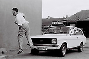 Peter McGowen heading a ball away from a Ford Escort, Southall, UK, 1987.