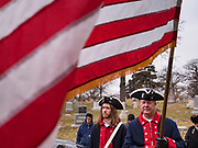 14 DECEMBER 2019 - DES MOINES, IOWA: MIKE ROWLEY, left, and RICK HICKMAN, both wearing uniforms of the Revolutionary War Continental Army, were the honor guard, with an American flag at the Christmas wreath laying ceremony in Woodlands Cemetery. Volunteers working with Wreaths Across America placed Christmas wreaths on the headstones of more than 600 US military veterans in Woodland Cemetery in Des Moines. The cemetery, one of the first in Des Moines, has the graves of veterans going back to the War of 1812.PHOTO BY JACK KURTZ
