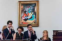 "© Licensed to London News Pictures. 24/06/2015. London, UK. Sotheby's staff bidding on behalf of their telephone clients for Pablo Picasso's ""Deux Personnages (La Lecture)"", which sold for a hammer price of £14.5m, within its estimate of £13-£18m. Sotheby's Impressionist & Modern art evening sale realised a total of £178.6m, the second highest total for any sale ever held in London.  Photo credit : Stephen Chung/LNP"
