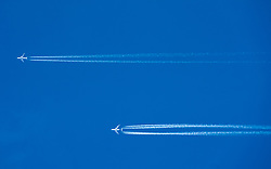 Two passenger jets leave contrails in blue sky