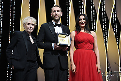 """Director Vasilis Kekatos receives the Short Film award for """"The Distance Between Us and The Sky"""" as Jury Members Claire Denis and Nadine Labaki look on on stage during the Closing Ceremony of the 72nd annual Cannes Film Festival on May 25, 2019 in Cannes, France. Photo by David Niviere/ABACAPRESS.COM"""