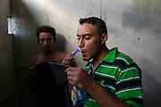 NUEVO LAREDO MEXICO - JUNE 27TH, 2014: A Central American immigrant shaves himself inside at Casa del Migrante Amar in Nuevo Laredo, Tamaulipas, Mexico, June 27th, 2014.  CREDIT: Rodrigo Cruz for The New York Times