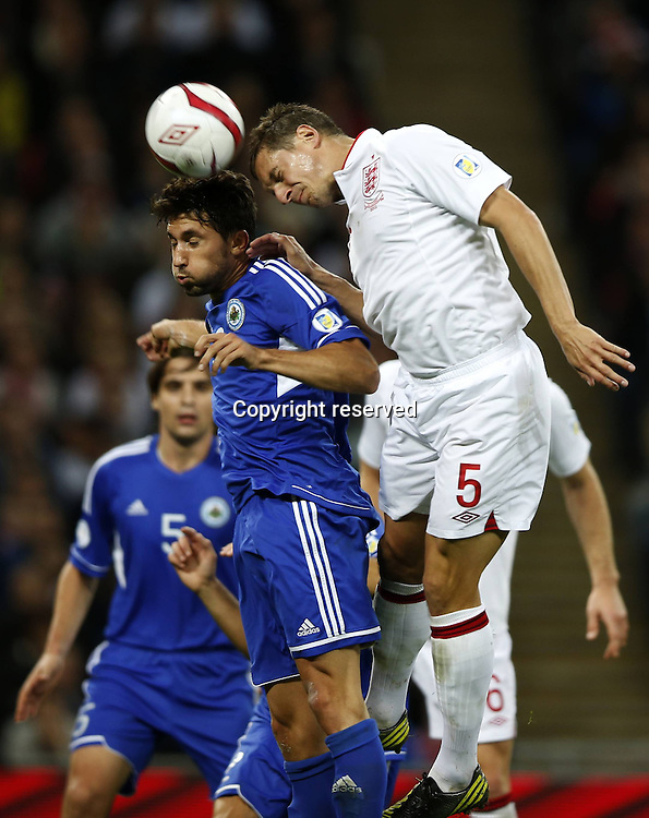 12.10.2012. Wembley Stadium, London, England.  Phil Jagielka r of England challenges  with Mirko Palazzi of San Marino during The FIFA 2014 World Cup Group H Qualifying Match between England and San Marino AT Wembley Stadium. England won the game by a score of 5-0.