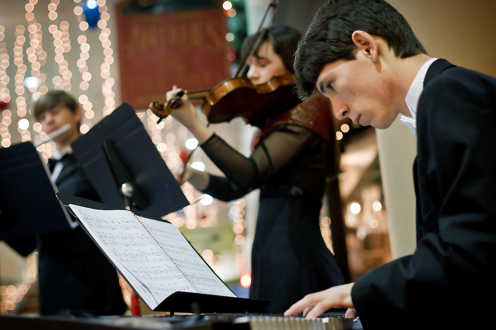 Andrew Maurer, 18, plays the piano alongside his twin sister, Alyssa Maurer, on the violin, and younger brother Shane Maurer, 15, on the flute, during a concert Wednesday in the Coeur d'Alene Resort Plaza Shops. The Kardia Trio played holiday songs to help raise funds for the Press Christmas for All program.