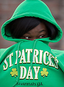 Chizzy Odimgbe keeps warm before the start of the St. Patrick's Day parade, Tuesday, March 17, 2015, in Savannah, Ga. The St. Patrick's Day tradition in Savannah dates back to the first parade held on March 17, 1824. While Savannah has been celebrating St. Patrick's Day for 191 years, there have been at least six years without a parade. (AP Photo/Stephen B. Morton)
