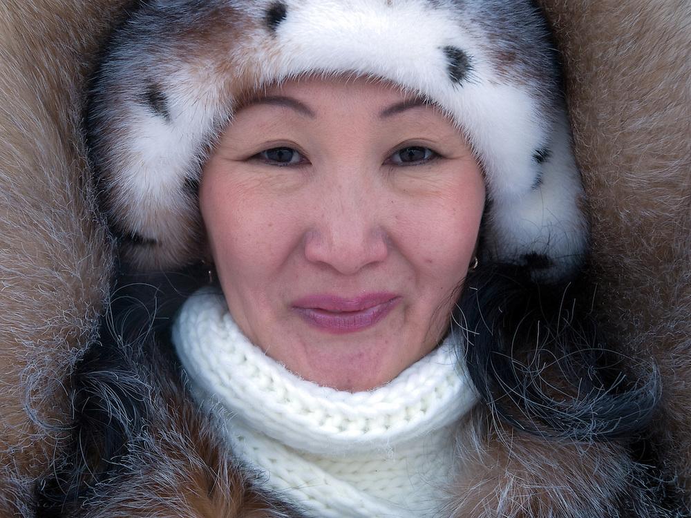 Jakutische Frau mit Kopfbedeckung gesch&uuml;tzt gegen die extreme Kaelte in der Innenstadt von Jakutsk. Jakutsk wurde 1632 gegruendet und feierte 2007 sein 375 jaehriges Bestehen. Jakutsk ist im Winter eine der kaeltesten Grossstaedte weltweit mit durchschnittlichen Winter Temperaturen von -40.9 Grad Celsius. Die Stadt ist nicht weit entfernt von Oimjakon, dem Kaeltepol der bewohnten Gebiete der Erde.<br /> <br /> Yakut women protected with headgears against the extrem climate  in the city center of Yakutsk. Yakutsk was founded in 1632 and celebrated 2007 the 375th anniversary - billboard announcing the celebration. Yakutsk is a city in the Russian Far East, located about 4 degrees (450 km) below the Arctic Circle. It is the capital of the Sakha (Yakutia) Republic (formerly the Yakut Autonomous Soviet Socialist Republic), Russia and a major port on the Lena River. Yakutsk is one of the coldest cities on earth, with winter temperatures averaging -40.9 degrees Celsius.