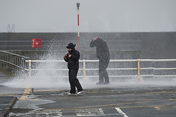 "© London News Pictures. 08/02/2014. Aberystwyth, UK. <br /> A couple get fought in a wave as gale force winds strike the sea walls at Aberystwyth, Wales at high tide. The winds are forecast to strengthen throughout the day, gusting up to 70 or 80 mph, and with the rising tide, their impact could be potentially damaging again. An amber ""be prepared"" warning  has been issued by the Met Office for wind,. Photo credit: Keith Morris/LNP"