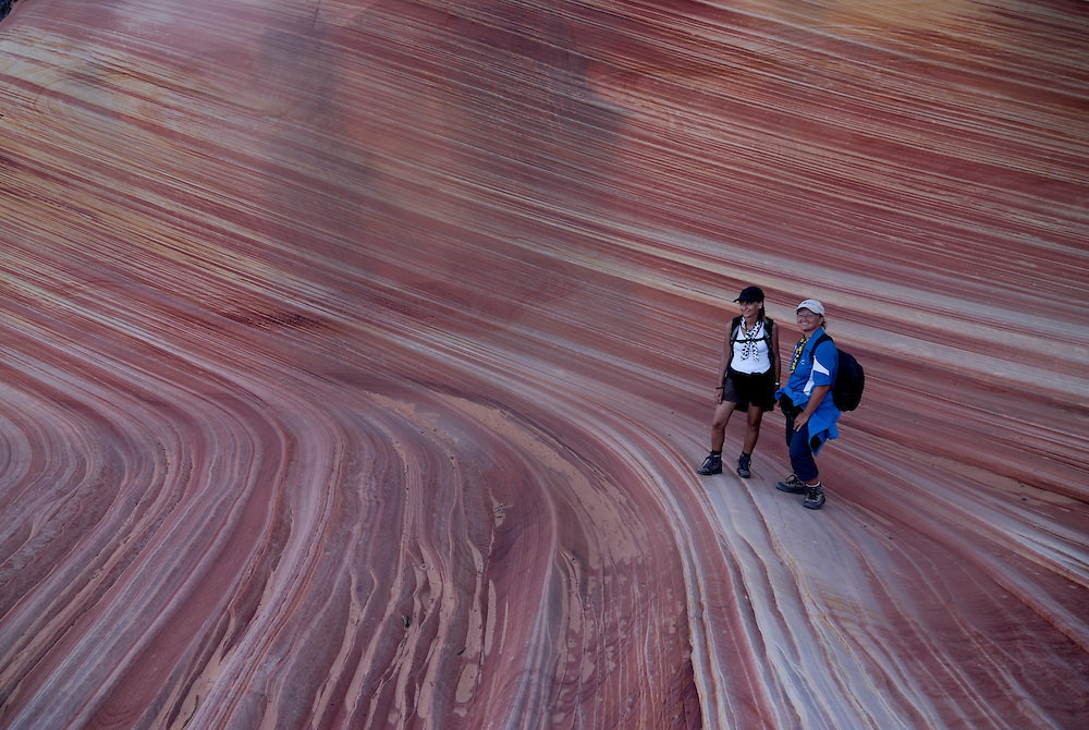"Tourist walking through the beautiful rock formation ""The wave"", Vermillion Cliffs, Utah, USA, MR"