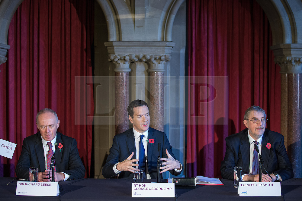© Licensed to London News Pictures . 03/11/2014 . Manchester , UK . Sir Richard Leese , The Chancellor of the Exchequer , George Osborne MP and Lord Peter Smith at Manchester Town Hall signing a deal to devolve power to Greater Manchester , including giving the city a Mayor and greater control over its finances . Photo credit : Joel Goodman/LNP