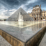 Sunbathers relax alongside the main Pyramid of the Louvre in Paris, one of the city's most famous landmarks