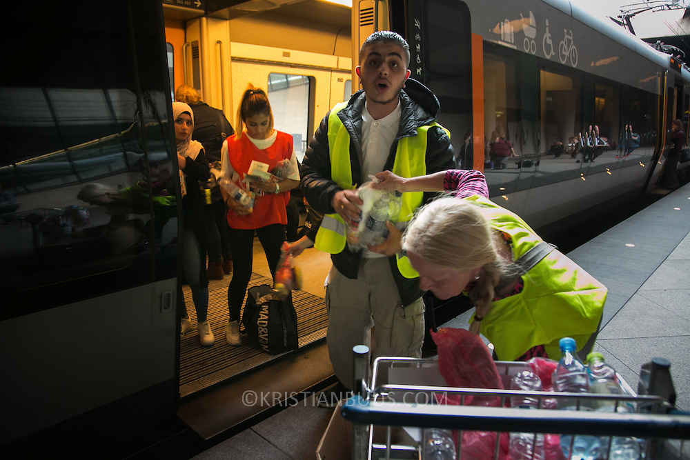 The train only stops briefly on the way to Sweden and the volunteers try to supply refugees on board with food and drinks in the short time they have before the doors will shut again.  This train has got babies onboard and baby supplies are called for. An unprecedented number of refugees arrived from Germany in early September, most being Syrian war refugees, some from Afghanistan. Most wanted to travel on to Sweden and a number of Danish citizens created a spontanious network to assist the refugees with travel, food, clothes and psycological support.