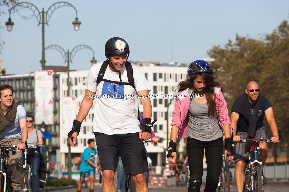Brussels 2012 september 16 This Sunday the entire province of Brussels was forbidden for cars. All roads were free to use by foot, by bike or anyway you like. Public transport did work, but were free. In Brussels pedestrians and cars are a hot issue for many years now. Cars are everywhere, making Brussels one of the most polluted capitals of Europe. Guy on a rental bike looking in camera.