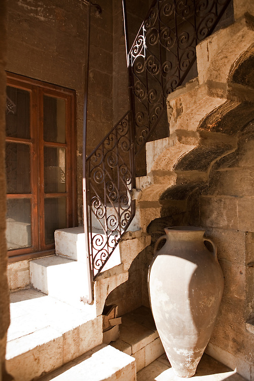 Sunlight creates shadows on an urn, a staircase, and a railing in an old Aleppo home, Syria