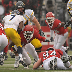 Dec 5, 2009; Piscataway, NJ, USA; Rutgers linebacker Steve Beauharnais (42) upends West Virginia running back Noel Devine (7) during first half NCAA Big East college football action between Rutgers and West Virginia at Rutgers Stadium.