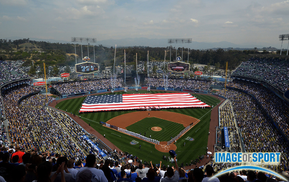 Apr 4, 2014; Los Angeles, CA, USA; General view of the playing of the national anthem with a United States flag on the field before the 2014 season home opening game between the San Francisco Giants and Los Angeles Dodgers at Dodger Stadium.