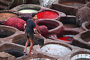 View from behind of worker with bucket amongst the dyeing pits, Chouara tannery, Fez, Morocco, pictured on February 25, 2009 in the evening. The Chouara tannery is the largest of the four ancient tanneries in the Medina of Fez where the traditional work of the tanners has remained unchanged since the 14th century. It is composed of numerous dried-earth pits where raw skins are treated, pounded, scraped and dyed. Tanners work in vats filled with various coloured liquid dyes derived from plant sources. Colours change every two weeks, poppy flower for red, mint for green, indigo for blue, chedar tree for brown and saffron for yellow. Fez, Morocco's second largest city, and one of the four imperial cities, was founded in 789 by Idris I on the banks of the River Fez. The oldest university in the world is here and the city is still the Moroccan cultural and spiritual centre. Fez has three sectors: the oldest part, the walled city of Fes-el-Bali, houses Morocco's largest medina and is a UNESCO World Heritage Site;  Fes-el-Jedid was founded in 1244 as a new capital by the Merenid dynasty, and contains the Mellah, or Jewish quarter; Ville Nouvelle was built by the French who took over most of Morocco in 1912 and transferred the capital to Rabat. Picture by Manuel Cohen.