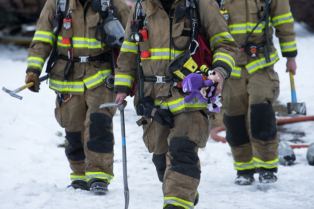 GABE GREEN/Press<br /> <br /> A firefighter carries children&rsquo;s toys from an apartment complex in the 4200 block of North Crown Avenue which caught fire early Friday morning. Six children were taken to Kootenai Health for treatment of injuries