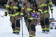 GABE GREEN/Press<br /> <br /> A firefighter carries children's toys from an apartment complex in the 4200 block of North Crown Avenue which caught fire early Friday morning. Six children were taken to Kootenai Health for treatment of injuries