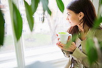 Young businesswoman with coffee cup looking through window at office