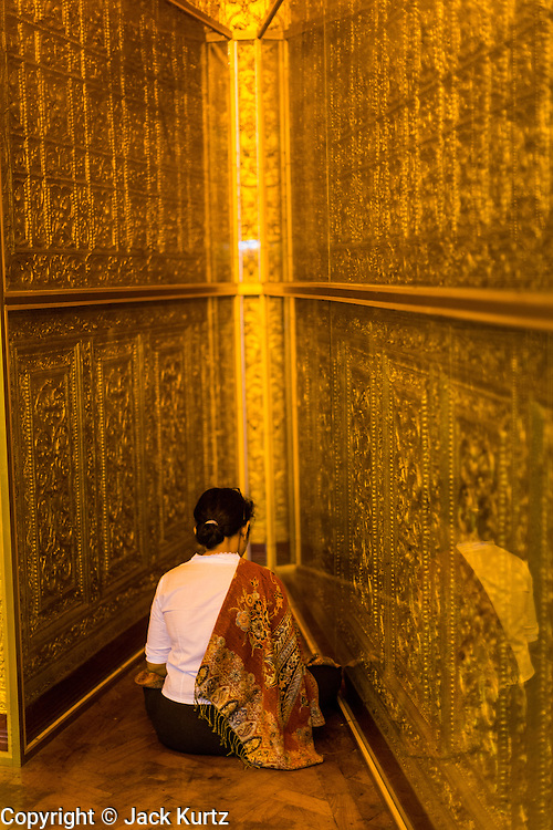 04 JUNE 2014 - YANGON, YANGON REGION, MYANMAR: A woman prays in Botataung Paya (Pagoda) in Yangon, Myanmar (Rangoon, Burma). Botataung is one of the most famous pagodas in Yangon with maze like interior of gold leaf covered walls. The pagoda houses a hair from the Buddha and is one of the most sacred sites in Burma. Yangon, with a population of over five million, continues to be the country's largest city and the most important commercial center.     PHOTO BY JACK KURTZ