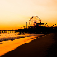 Santa Monica Pier sunset panorama picture over the Pacific Ocean in Southern California. Santa Monica Pier is a landmark that has an amusement park with a ferris wheel, roller coaster, restaurants, and other attractions. Panoramic photo ratio is 1:3.