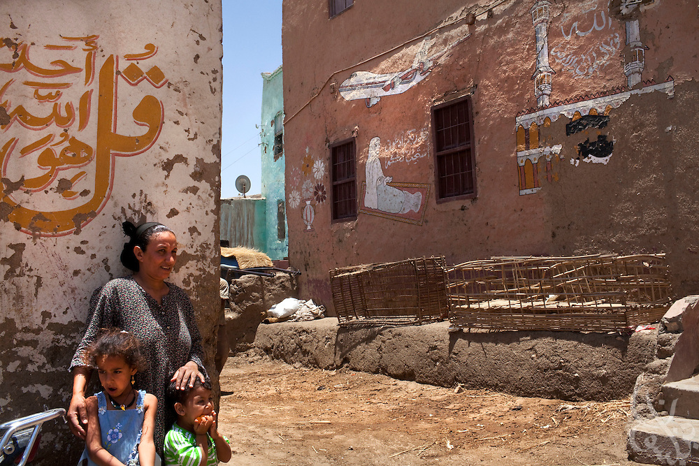 An Egyptian woman holds her children outside the family's traditional house June 6, 2009 in the village of Gourna on the West bank of the Nile river near Luxor. Several  families in this the village are among the last to hold out from Egyptian authorities plans to forcibly resettle all the residents of this area as part of a 30 year, 5 billion egyptian pound redevelopment plan. (Photo by Scott Nelson, for the Times)