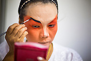 08 FEBRUARY 2013 - BANGKOK, THAILAND:   A woman puts on her makeup before performing a Teochew opera for Chinese New Year at Seacon Square in Bangkok. Chinese opera is popular in Thailand and is usually performed in the Teochew language. The weeks surrounding Chinese New Year are important for retailers in Thailand and many malls put on special promotions and events honoring Chinese culture, like Lion Dances or Chinese Opera. Thailand has a large Thai-Chinese population. Millions of Chinese emigrated to Thailand (then Siam) in the 18th and 19th centuries and brought their cultural practices with them.  PHOTO BY JACK KURTZ